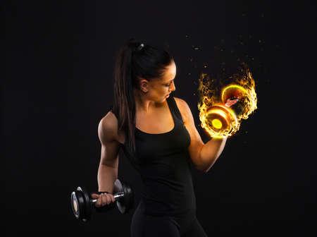 Junge sportslooking nette Dame mit dem dunklen Haar zeigt verschiedene führt Übungen mit Geräten auf dem schwarzen Hintergrund im Studio