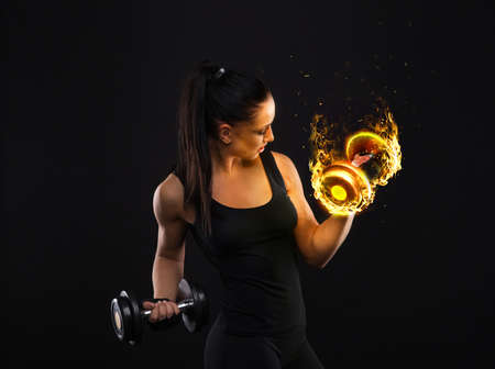 Young sportslooking nice lady with dark hair shows various performs exercises with equipment on the black background in studio Stock Photo