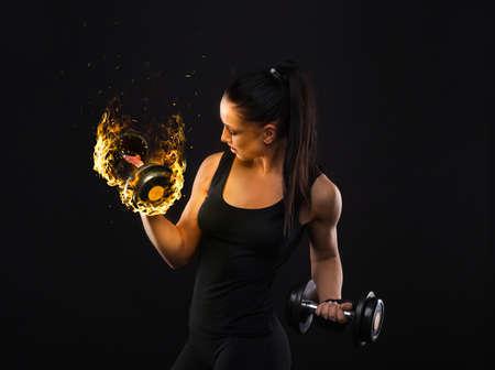 검은 머리와 젊은 sportslooking 좋은 여자는 스튜디오에서 검은 색 바탕에 장비와 다양한 수행 운동을 보여줍니다 스톡 콘텐츠
