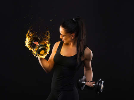 Young sportslooking nice lady with dark hair shows various performs exercises with equipment on the black background in studio Standard-Bild