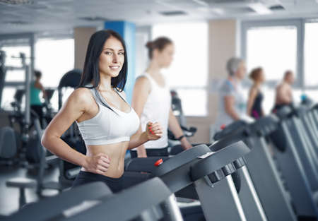 young sexy lady running on treadmill in gym