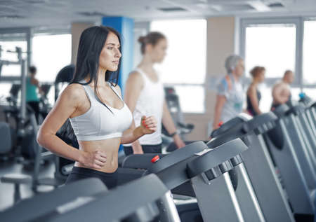 treadmill: young sexy lady running on treadmill in gym