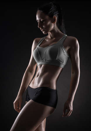 sculpted: Young fitness woman showing her perfect sculpted muscular and tight body