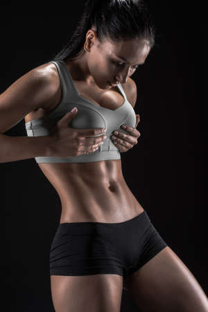 tight body: Young fitness woman showing her perfect sculpted muscular and tight body