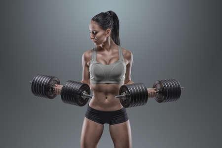 Fitness Mädchen mit Hanteln auf einem grauen Hintergrund