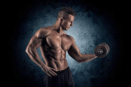 musculation: Handsome power athletic man bodybuilder doing exercises with dumbbell. Fitness muscular body on dark background.