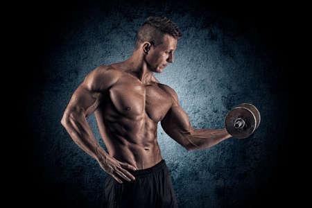 Poder guapo hombre atlético culturista haciendo ejercicios con mancuernas. Musculoso cuerpo fitness en el fondo oscuro.