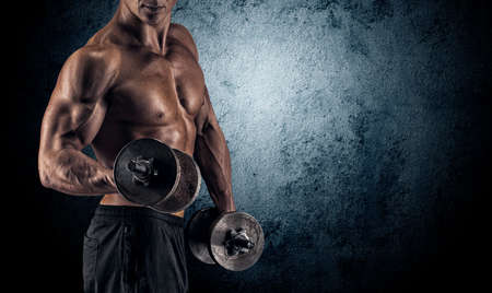 deportista: Poder guapo hombre atl�tico culturista haciendo ejercicios con mancuernas. Musculoso cuerpo fitness en el fondo oscuro.