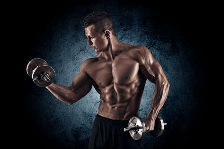 vigorously: Handsome power athletic man bodybuilder doing exercises with dumbbell. Fitness muscular body on dark background.