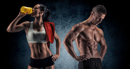 fitness trainer: Bodybuilding. Strong man and a woman posing on a dark background Stock Photo