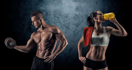 Bodybuilding. Strong man and a woman posing on a dark background Standard-Bild