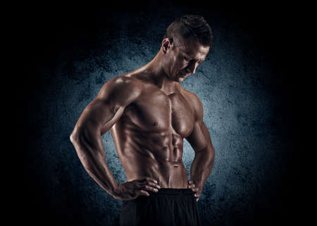 musculation: Muscular young man in studio on dark background shows the different movements and body parts