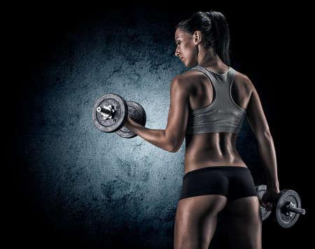 어두운 배경에 스튜디오에서 근육 젊은 여자가 다른 운동과 신체 부위를 보여줍니다