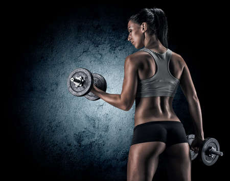Muscular young woman in studio on dark background shows the different movements and body parts Stock Photo