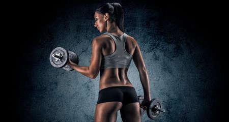 Muskulöse junge Frau im Studio auf dunklem Hintergrund zeigt die verschiedenen Bewegungen und Körperteile