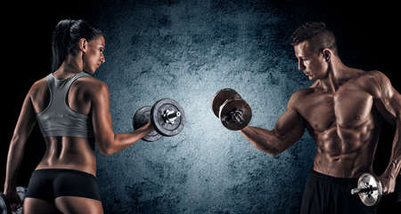 muscle woman: Man and woman isolated on a dark background Stock Photo