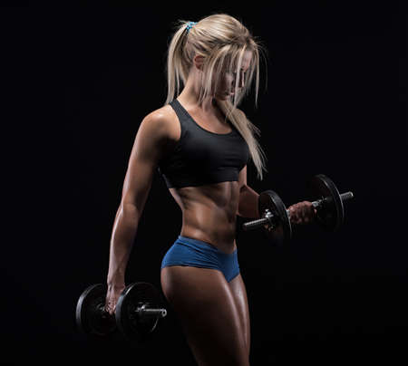 strength: Fitness girl with dumbbells on a dark background