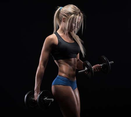 fuerza: Muchacha de la aptitud con pesas sobre un fondo oscuro Foto de archivo