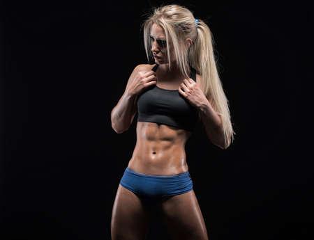 그녀의 완벽한 조각 근육과 단단한 몸을 보여주는 젊은 피트 니스 여자