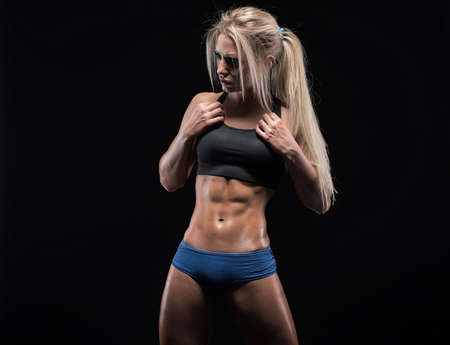 female body: Young fitness woman showing her perfect sculpted muscular and tight body
