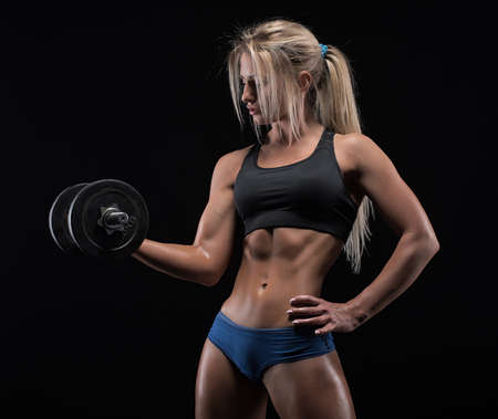strong women: Fitness girl with dumbbells on a dark background