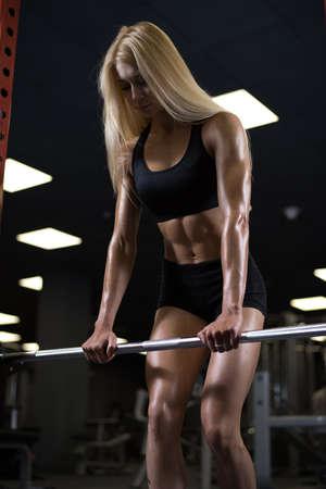 Athletische junge Frau, die Ruhe während des Trainings in der Turnhalle