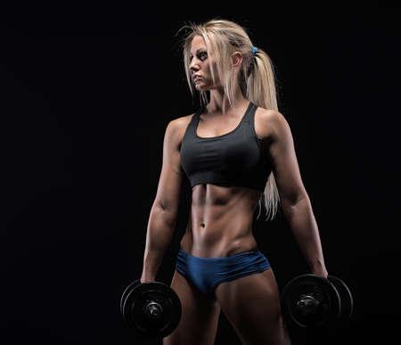 Fitness Mädchen mit Hanteln auf einem dunklen Hintergrund Lizenzfreie Bilder