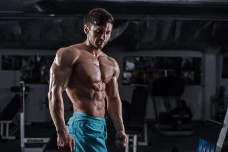 fitness hombres: Bodybuilder hermoso funciona empujando hacia arriba ejercicio en el gimnasio