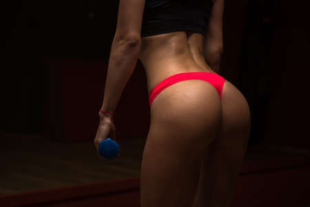 short shorts: Beautiful sexy girl in short shorts and a tank top posing in the gym