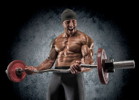 barbel: Handsome power athletic man bodybuilder doing exercises with barbell. Fitness muscular body on dark background.
