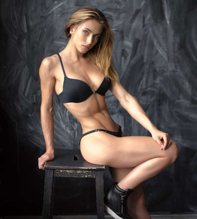 area sexy: Beautiful young athletic girl in underwear with Spanish looks on a dark background