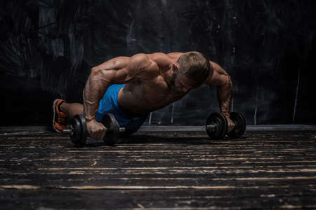 Handsome muscular man bodybuilder posing in the studio on a darck background