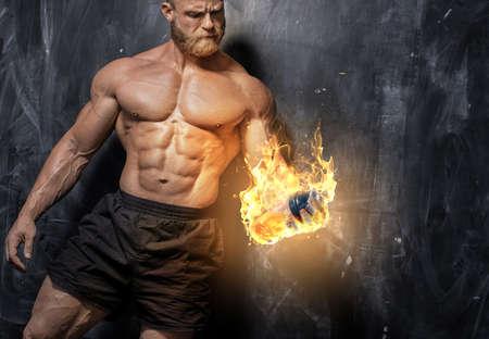 Handsome power athletic man bodybuilder. Fitness muscular body on dark background. Фото со стока
