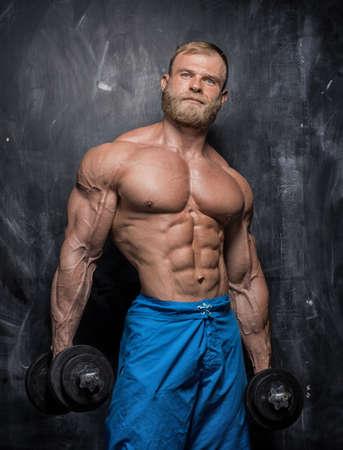 darck: Handsome muscular man bodybuilder posing in the studio on a darck background