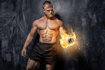 Handsome power athletic man bodybuilder. Fitness muscular body on dark background. Standard-Bild