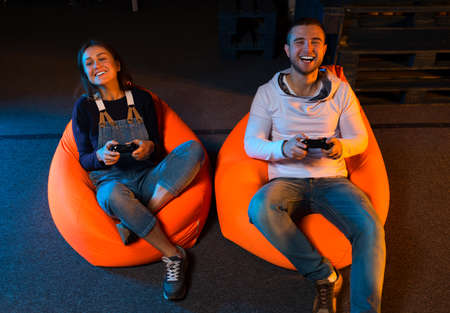 gamers: Playing video games while sitting on sofa