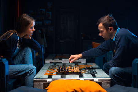Young people playing chess in the games room Banco de Imagens
