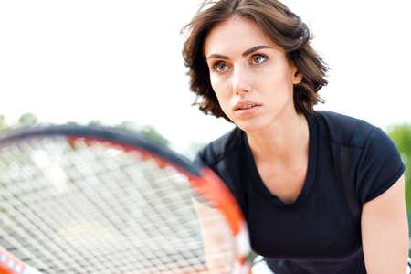 Beautiful young girl on an open tennis court playing tennis