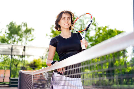 Beautiful young girl on an open tennis court playing tennis