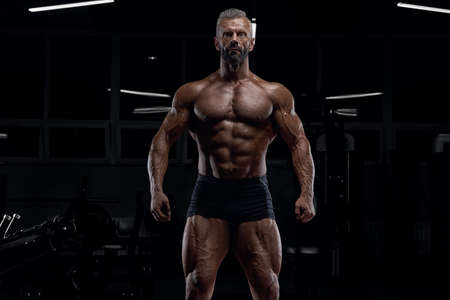 Brutal adult athlete posing in the gym. Fitness muscled man.