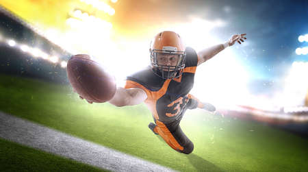 American football player at the stadium in black and orange outfit. Stock Photo