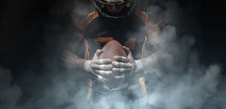 American football player on a dark background in smoke in black and orange equipment. Stock Photo