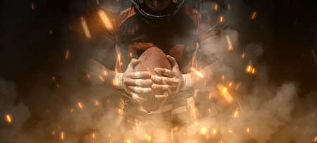 American football player on dark background in smoke and sparks in black and orange outfit. Stock Photo