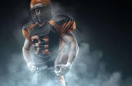 American football player on a dark background in smoke in black and orange equipment. 版權商用圖片