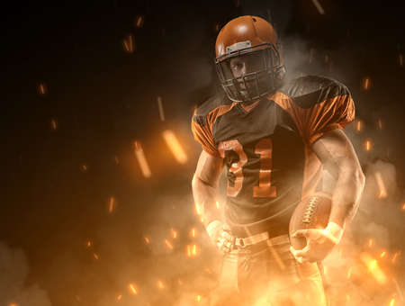 American football player on dark background in smoke and sparks in black and orange outfit. Stok Fotoğraf