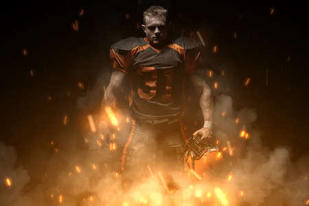 American football player on dark background in smoke and sparks in black and orange outfit. 版權商用圖片