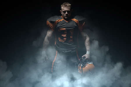 American football player on a dark background in smoke in black and orange equipment. 版權商用圖片