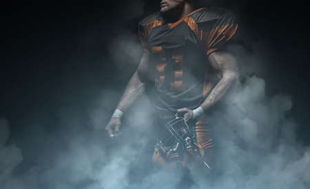 American football player on a dark background in smoke in black and orange equipment. 免版税图像