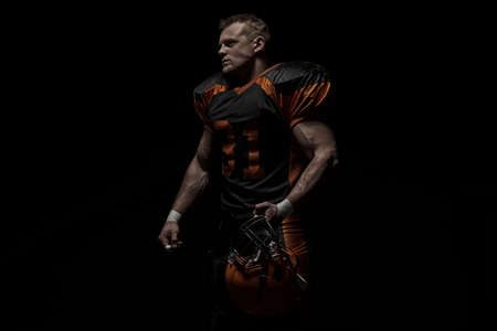 American football player on a dark background in black and orange equipment. 免版税图像