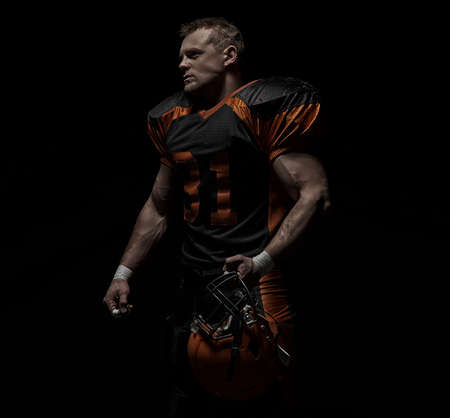 American football player on a dark background in black and orange equipment. 版權商用圖片